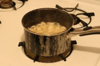 A pot of rawhide and water being heated on top of the kitchen stove.