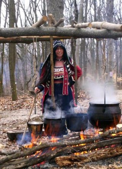 An Ojibwa woman in traditional drss demonstarting how to boil maple syrup over an open fire using iron pots.