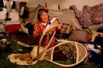 Photo of a mand making bearpaw snowshoes.